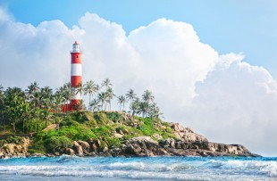 Lighthouse on the rocks near the ocean at blue sky with big white clouds in Kovalam, Kerala, India copy