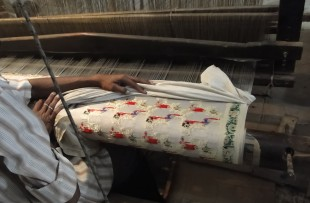 Young muslim man runs a loom to weave silk brocade