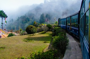 Train passing a beautiful garden and entering into fog. Surrounded by tree covered mountains copy